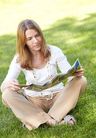 Beautiful woman reading a magazine in the summer park photo