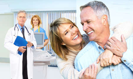 Smiling medical doctor with stethoscope and elderly couple  photo