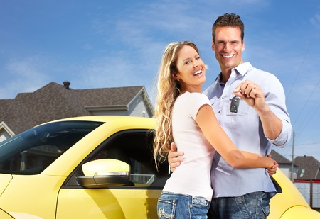 purchase: Happy young couple near new car with a key. Stock Photo