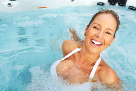 jacuzzi: Beautiful woman relaxing in a hot tub. Vacation.