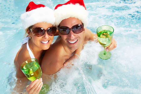 tub: Happy christmas santa couple in hot tub. Vacation.