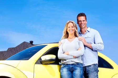 rent car: Happy young couple near a new yellow car. Stock Photo