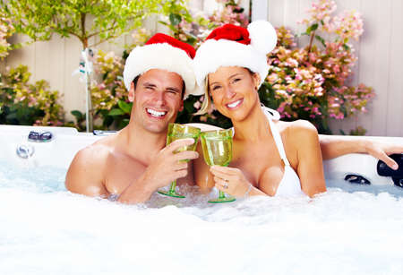 Happy christmas santa couple in hot tub. Vacation. photo