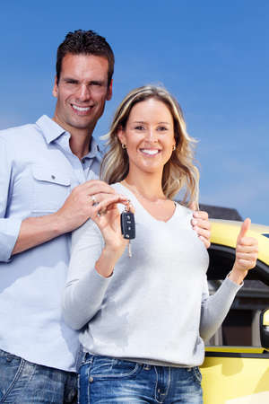 yellow car: Happy young couple near new car with a key. Stock Photo