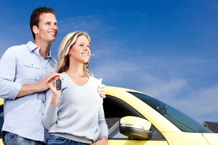 auto leasing: Happy young couple near new car with a key. Stock Photo