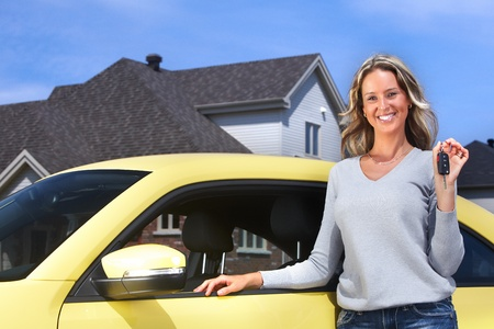 Happy young woman near new car with a key. photo