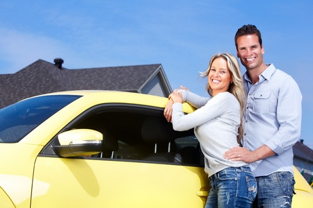 Young happy couple near new yellow car. photo