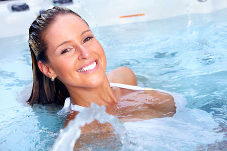 jacuzzi: Happy woman relaxing in hot tub. Vacation.