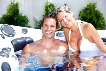 hydrotherapy: Happy couple relaxing in hot tub. Vacation. Stock Photo
