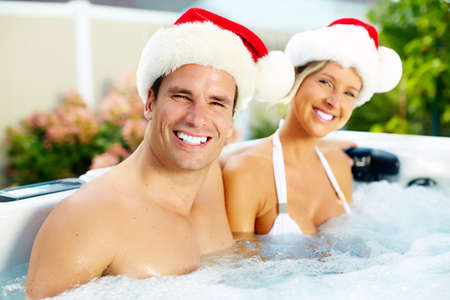 pool party: Happy christmas santa couple in hot tub. Vacation.