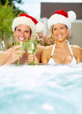 fiesta familiar: Feliz navidad de santa pareja en el jacuzzi. Vacaciones.