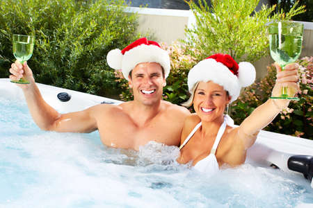 bathtub: Happy christmas santa couple in hot tub. Vacation.