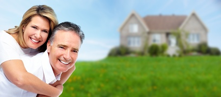 mortgages: Happy senior couple near new house. Real estate background.