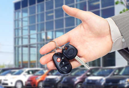 car dealers: Hand giving a car key. Auto repair service.