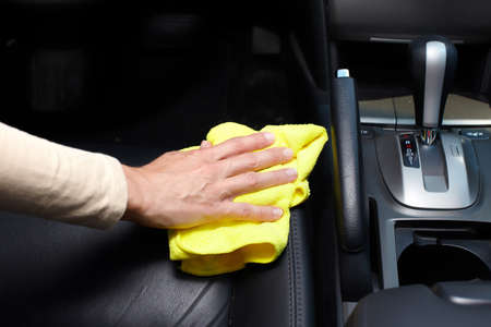 car cleaning: Hand cleaning car seat. Stock Photo