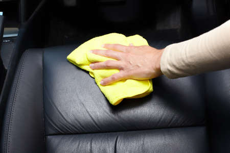 car clean: Hand cleaning car seat. Stock Photo