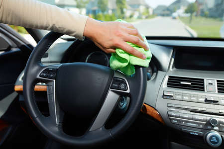 car in garage: Hand with microfiber cloth cleaning car.