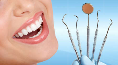 Beautiful woman Teeth with dental tools. photo