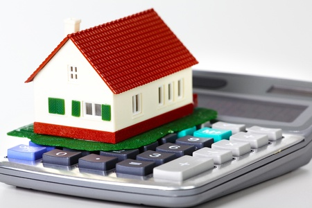 calculations: House and calculator. Real estate concept background.