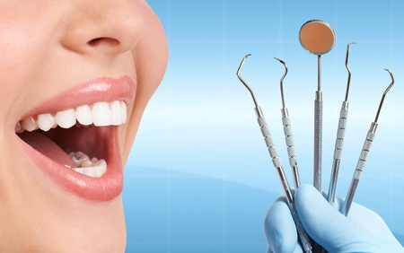 Beautiful woman Teeth with dental tools. photo