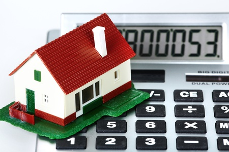 housebuilding: House and calculator. Real estate concept background.