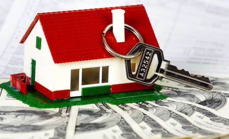 housebuilding: Family house with money and key. Real estate background. Stock Photo