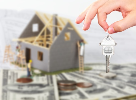 housebuilding: Family house with money and key. Construction background. Stock Photo