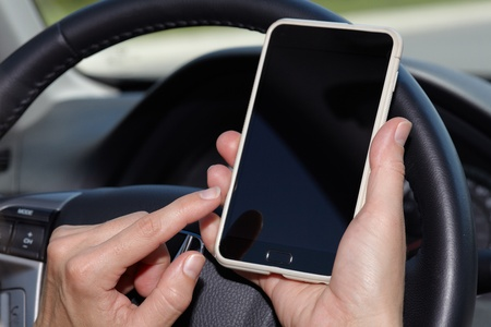 phone: Car driver hands with cell phone. Driving. Stock Photo