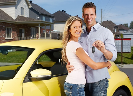 new automobiles: Happy young couple near new car with a key  Stock Photo