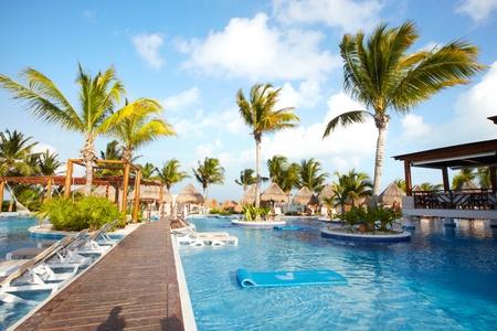 Swimming pool at caribbean resort. Exotic garden.