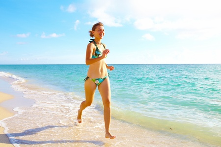 Woman running on Miami beach  Vacation  photo