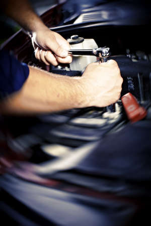 workshops: Hands of car mechanic in auto repair service.