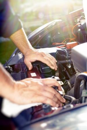 car maintenance: Hands of car mechanic in auto repair service.