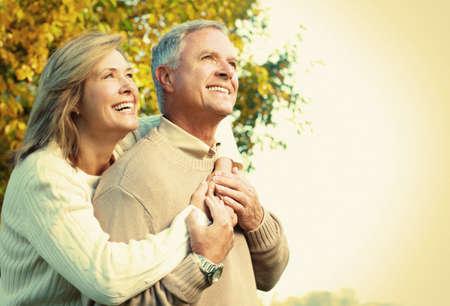 embracing couple: Feliz pareja senior se relaja en el parque Foto de archivo