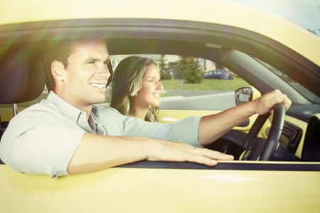 Two young smiling people in a yellow car photo