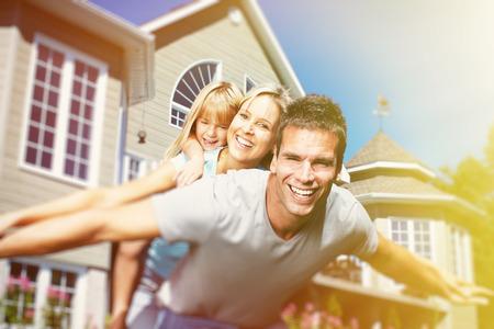 pareja en casa: Familia sonriente feliz con el ni�o sobre fondo casa Foto de archivo