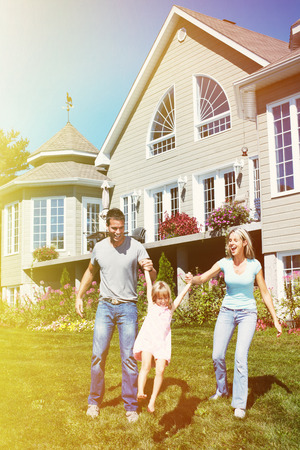 Happy smiling family with child over  house background photo