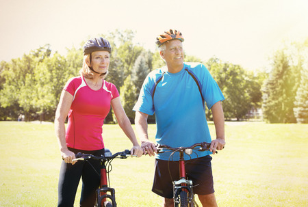 bycicle: Two aged people with bycicle over park background