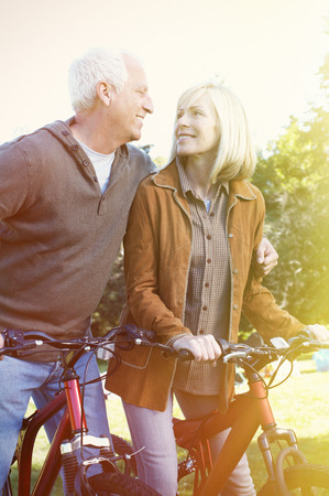 bycicle: Two aged smiling people with bycicle over park background Stock Photo