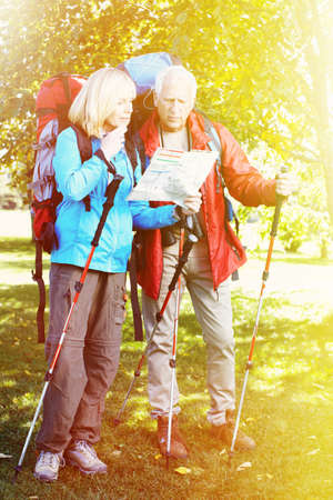 Two aged people with rucksacks looking for way photo
