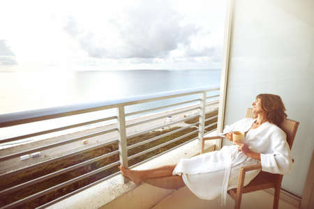 balcony: Woman drinking coffee in hotel terrace over sea view
