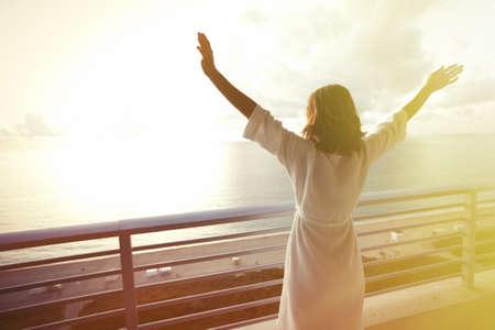 Gelukkige vrouw met handen omhoog naar de hemel kijken naar de oceaan