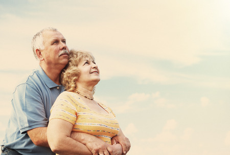 Two aged smiling people over sky background photo