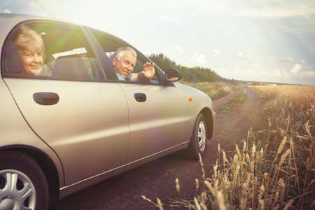 Driving: Two elderly people in car in field Stock Photo