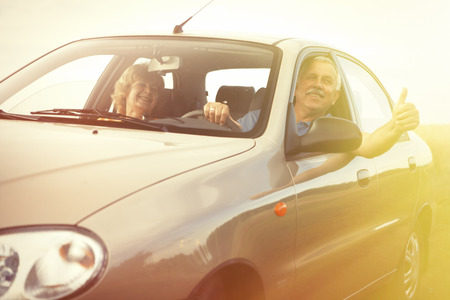 Two happy smiling elderly people in car pointing thumb photo