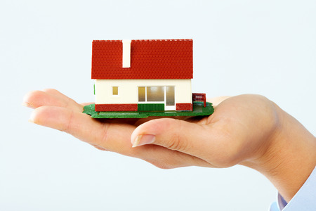 housebuilding: Hands holding Family house model. Real estate background. Stock Photo