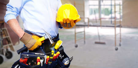 helmets: Worker with a tool belt. Isolated over white background.