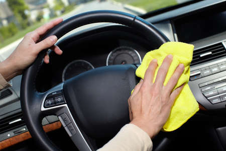 service car: Hand with microfiber cloth cleaning car.