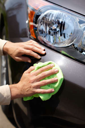 headlights: Hand with microfiber cloth cleaning car.