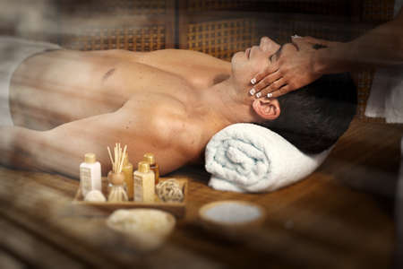 Handsome man relaxing in spa massage salon. photo